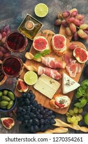 Appetizers table with italian antipasti snacks and wine in glasses . Traditional italian bread sticks grissini with prosciutto ham, figs, grapes, cheese, olives.Top view.