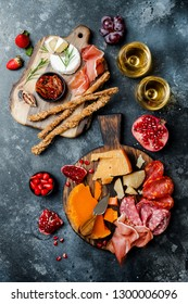 Appetizers table with italian antipasti snacks and wine in glasses. Brushetta or authentic traditional spanish tapas set, cheese variety board over black stone background. Top view, flat lay