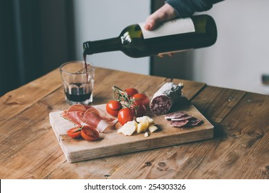 Appetizers - tomato, meat and cheese - on wooden board with bottle of wine and glass. Toned image