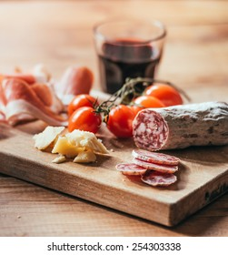 Appetizers - tomato, meat and cheese - on wooden board with  glass of wine