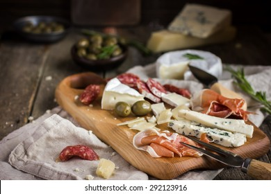 Appetizers. Various types of cheese, salami and prosciutto on  wooden cutting board, rustic background