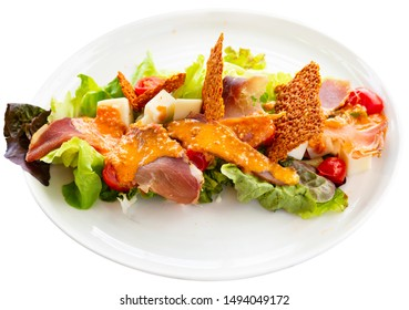 Appetizing Basque salad with sheep cheese, cured ham, romaine salad and tomatoes. French cuisine. Isolated over white background