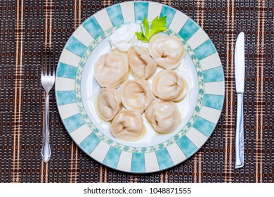 appetizing boiled perogies with sour cream on a large beautiful plate with a green fresh leaf, a metal knife and fork lie on the edges, a wicker mat in the background
