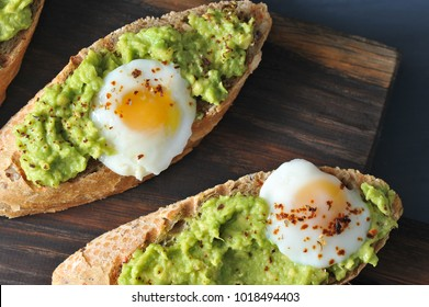 Appetizing bruschetta with egg and avocado on a wooden board. On the fried baguette, the avocado pulp and fried quail egg. Dark background. View from above. Close-up. Macro photography.