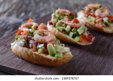 Appetizing bruschetta with a garnish of finely chopped mix of various fresh vegetables, avocados, decorated with shrimps on top, are on a wooden board