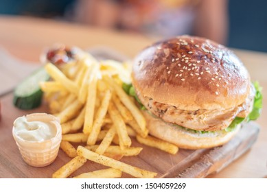 appetizing burger and fries on a wooden board. selective focus.