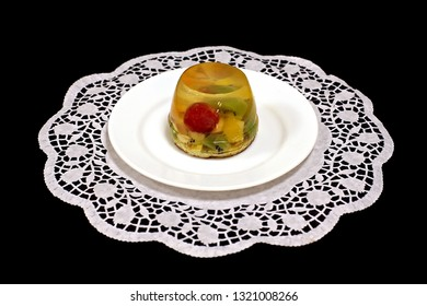Appetizing cake with jelly grapes of kiwi and mandarin on a white napkin. Close-up. On a dark background.