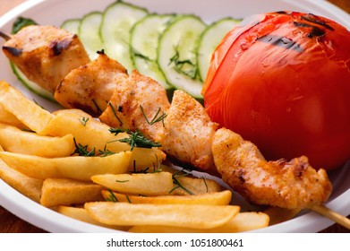 appetizing chicken kebab, fried potatoes chips,  grilled tomato and fresh sliced cucumbers close-up on white plate