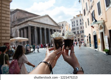 Appetizing coffee ice cream in female hands over Pantheon city view, Rome, Italy. Tasty ice cream like a symbol of summer and italian dessert over roman street.