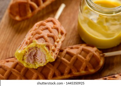 Appetizing corn dogs with mustard dip, close up. Juicy sausage covered with waffle butter. Trendy fast food.