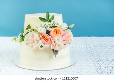 appetizing creamy white two-tiered wedding cake decorated with fresh flowers on a table with a lace tablecloth in studio on a blue background