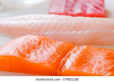 Appetizing fish fillets on a white cutting board. Rockfish, salmon and tuna, close-up. Sushi restaurant.