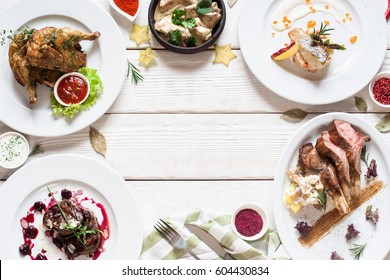 Appetizing frame of restaurant meals flat lay. Top view on assortment of meat and fish dishes, free space on white wooden table. Menu, healthy eating, buffet concept