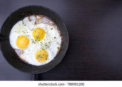 appetizing fried eggs in an old frying pan