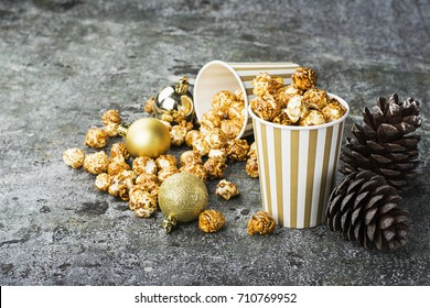 Appetizing golden caramel popcorn in paper striped cups in the New Year's interior with fir cones, New Year's golden balls on a gray stone modern background. Selective focus.