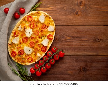 Appetizing golden focaccia with tomatoes, chiken meat, spices on dark wooden rustic table, top view, copy space