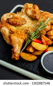 appetizing grilled chicken with homemade potatoes and sauce on a black tray