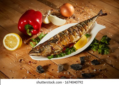 Appetizing grilled fish with vegetables on wooden background. Homemade smoked mackerel fish. Appetizing scomber prepared on tandoor (barbecue) on a brown rustic wooden table.