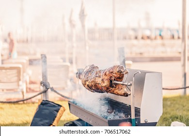 Appetizing grilled lamb on the spit skewer, roasted on traditional barbecue with hot charcoal.Roasting prepared ram duck baked meat Whole carcass roasting over coals outdoor catered event street food