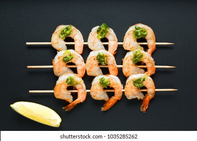 Appetizing grilled queen prawns  on wooden skewers with sauce. Shrimp barbecue top view on a black background
