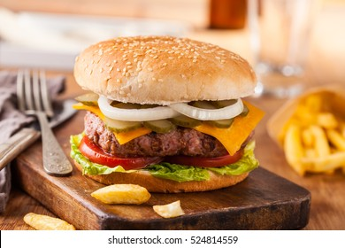 Appetizing hamburger with fries, beer on wooden cutting board. Pickles, onion, and cheddar cheese.