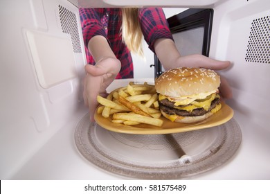 Appetizing hamburger and fries on plate inside the microwave. Girl heats food using the oven