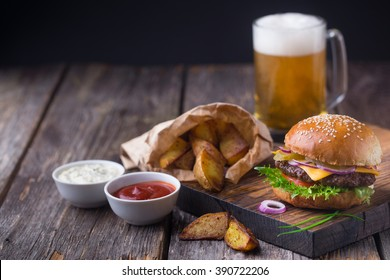 Appetizing homemade burger with beef patty, lettuce, tomato, cheese, pickled cucumbers and red onion served with fried potato, white sauce and ketchup, on wooden cutting board. With mug of light beer