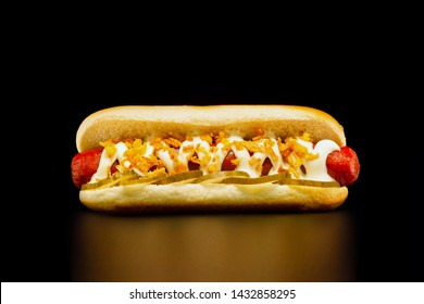 Appetizing hot dog with grilled beef sausage , pickles, mayonnaise and fried onions on black background.