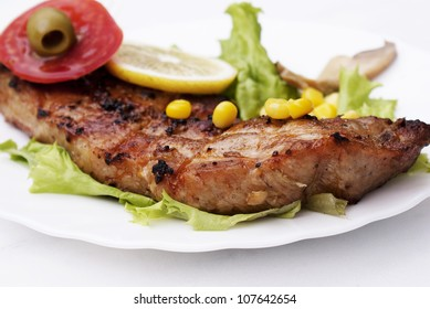 Appetizing juicy fried meat with green salad and marinaded vegetables