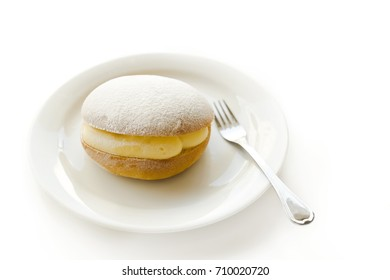 Appetizing loaf with custard cream and sugar powder served on plate with fork.