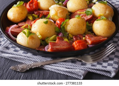Appetizing new potatoes with bacon and herbs, horizontal close-up