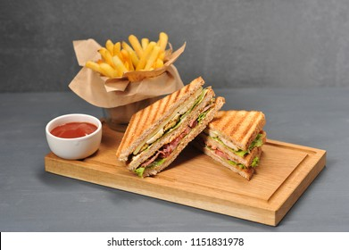 Appetizing and nutritious sandwich with a filling of bacon, chicken breast, cheese and fresh vegetables. Complementary sandwich crispy french fries and ketchup. Gray background. Close-up.