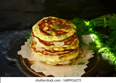 Appetizing pancakes on a wooden board. A photo of food in low key. Pancakes with parsley and chives. Ukrainian and Russian cuisine. Food on a black background. Pancake week.
