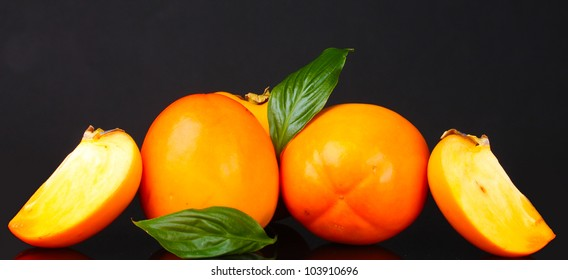 Appetizing persimmons with green leaves isolated on black