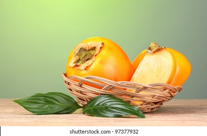 Appetizing persimmons with leaves in pad on wooden table on green background