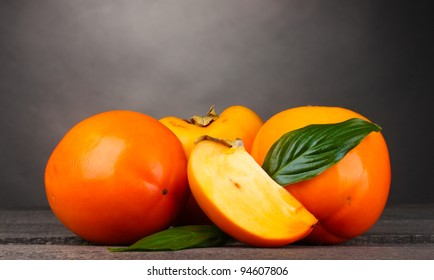 Appetizing persimmons on wooden table on grey background
