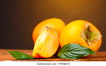 Appetizing persimmons on wooden table on brown background