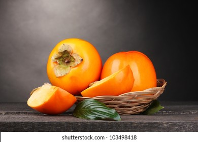 Appetizing persimmons in pad on wooden table on grey background