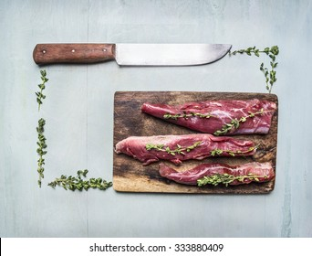 appetizing pieces of raw lamb with herbs and a knife on a cutting board lined rectangle on wooden rustic background top view close up