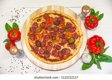 appetizing pizza with sausages and ham, spices and basil on a white table, flat lay