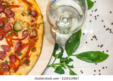 appetizing pizza with small sausages, basil and a glass of white wine on a white table