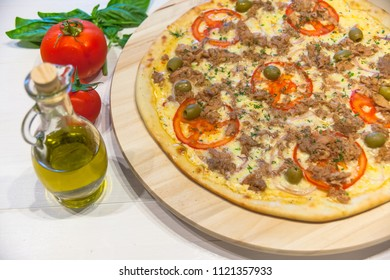 appetizing pizza with tuna, olive oil and basil leaves on a white table