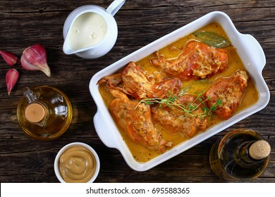 appetizing Rabbit Cooked with Dijon Mustard and white wine or lapin a la moutarde in gratin dish on old dark wooden table with ingredients on background, authentic french recipe, view from above