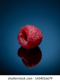Appetizing red raspberries on a blue background, close-up, macro.