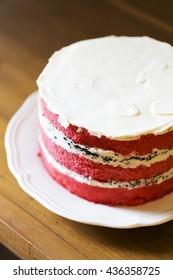 Appetizing red velvet cake on wooden table