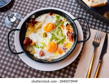 Appetizing Riojan style eggs casserole traditionally prepared with potatoes, bell peppers, sausages and piquant green sauce. Authentic Spanish cuisine