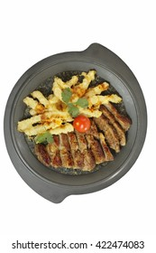 Appetizing roast pork with potatoes in batter on a metal plate on the white background.
