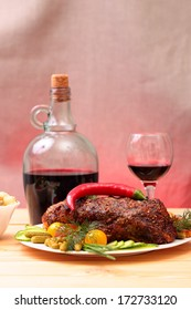 Appetizing roasted fillet of pork with spices, vegetables and bottle of wine