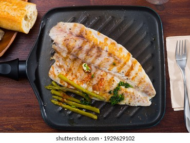 Appetizing roasted sea bass with asparagus served on grill pan