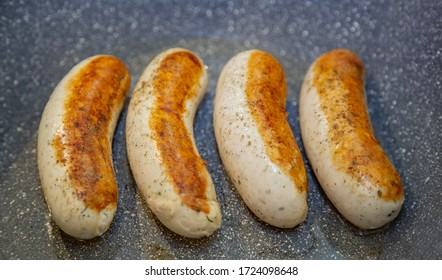 Appetizing ruddy juicy Munich sausages fried in a pan. Bavarian food style